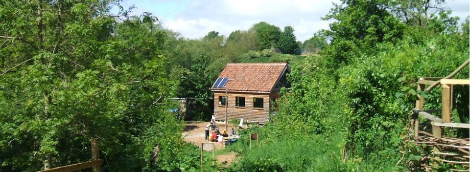 Building in St Werburghs CIty Farm with solar panel roof in the midst of Boiling Well's forest
