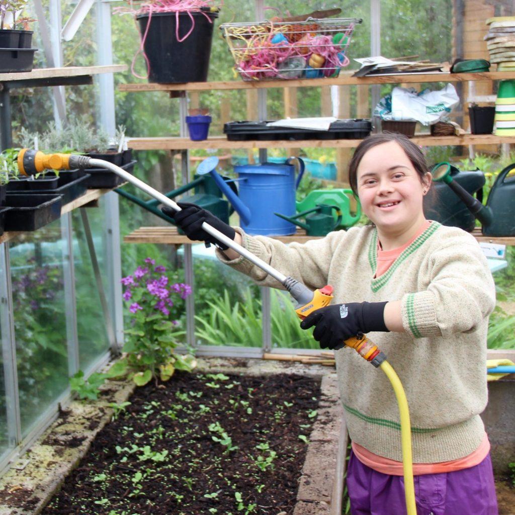 Volunteer watering plants in a greenhouse at St Werburghs City Farm
