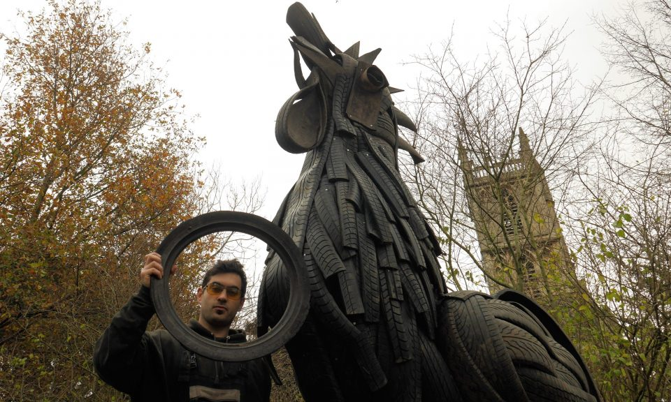 Artist djembello, creator of the Farm's tyre rooster, holding a bicycle tyre in front of rooster